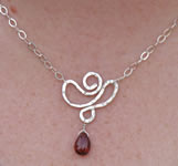 hand forged sterling lotus flower pendant with garnet briolette